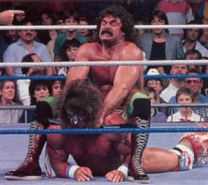 Rick Rude haciendo una llave a Ultimate Warrior.